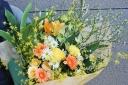 野の花屋 両手で抱える花束 イエローオレンジカラー