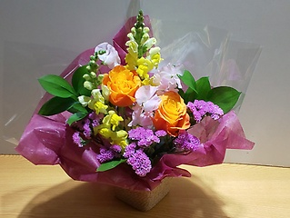 オレンジのバラをメインに、明るいアレンジメント