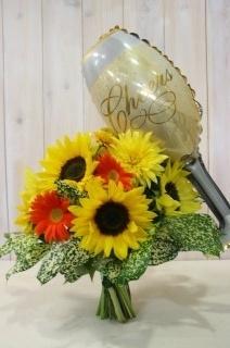 シャンパングラスとビタミンカラーの花束