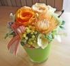 ライトグリーンのガラス花器にオレンジ系のお花♪