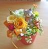 ネコちゃんがお花の間に座ったイエローオレンジプリザ
